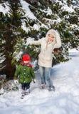 Macierzysty potrząsalny śnieg z gałąź na dziecku podczas gdy stojący outdoors Fotografia Stock