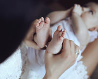 Macierzysty pozować z jej małym uroczym dzieckiem, trzyma jej cieki w rękach Fotografia Royalty Free