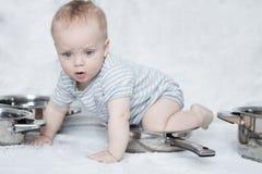 Macierzysty ` s pomagier w secie kucharstwo niecki i garnki Dziecięca chłopiec bawić się z setem naczynia Śliczny berbecia obsiad zdjęcia stock