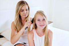 Macierzysty szczotkować długie włosy jej córka w domu obraz royalty free
