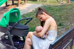 Macierzysty troskliwy dziecko w kochać ręki jest ubranym lata smokingowego obsiadanie na drewnianej ławce, breastfeeding dziecko  zdjęcie stock