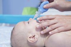 Macierzysty używa dziecko nosowy aspirator fotografia royalty free