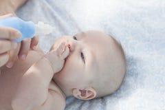 Macierzysty używa dziecko nosowy aspirator obrazy royalty free