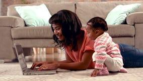 Macierzysty używa komputer z jej dzieckiem zdjęcie wideo