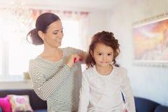 Macierzysty zgrzywiony włosy jej córka w ranku Obraz Stock