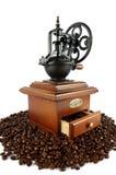 Macinacaffè antiquato con i chicchi di caffè isolati su bianco Fotografia Stock