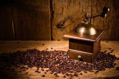 Macinacaffè anziano con i semi di cacao torrefatti freschi sul vecchio fondo d'annata rustico della quercia immagine stock libera da diritti
