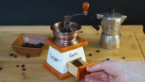 Macinacaffè manuale anziano che realizza il processo di molatura dei chicchi di caffè video d archivio