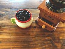 Macinacaffè manuale d'annata e chicchi di caffè scuri dell'arrosto in tazza Immagini Stock