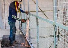 Macinazione elettrica della ruota di uso dell'uomo del lavoratore sulla rete metallica della struttura d'acciaio Fotografia Stock Libera da Diritti