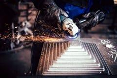 Macinazione elettrica della ruota sulla struttura d'acciaio in fabbrica industriale Acciaio di taglio del lavoratore fotografia stock libera da diritti