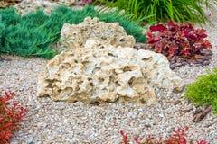 Macizo de flores con las piedras y los arbustos como elementos decorativos Fotografía de archivo libre de regalías