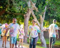 Painted Couple In Color Frenzy Fun Run. MACKAY, QUEENSLAND, AUSTRALIA - JUNE 2019: Unidentified couple covered in colored powder walk in Color Frenzy Fun Run royalty free stock image
