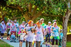 People Enjoying Color Frenzy Fun Run. MACKAY, QUEENSLAND, AUSTRALIA - JUNE 2019: Unidentified people in costume enjoy the Color Frenzy Fun Run. Woman carries stock photography