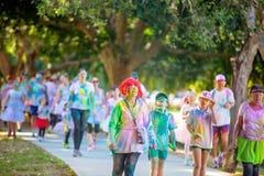 Woman In Red Wig Walks In Color Frenzy Fun Run. MACKAY, QUEENSLAND, AUSTRALIA - JUNE 2019: Unidentified senior woman in red wig splattered with colored powder stock photo