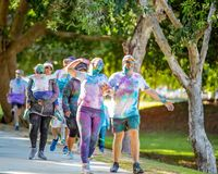 Couple Covered In Powder In Color Frenzy Fun Run. MACKAY, QUEENSLAND, AUSTRALIA - JUNE 2019: Unidentified woman covered in colored powder poses with partner in stock image