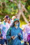 Woman Entrant In Color Frenzy Fun Run. MACKAY, QUEENSLAND, AUSTRALIA - JUNE 2019: Unidentified woman in hat and sunglasses covered all over in colored powder in royalty free stock image