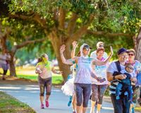 Woman Poses With Friends In Color Frenzy Fun Run. MACKAY, QUEENSLAND, AUSTRALIA - JUNE 2019: Unidentified woman posing as she walks with friends in Color Frenzy royalty free stock photo