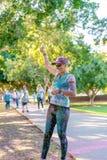 Woman Sprinkles Yellow Powder In Color Frenzy Fun Run. MACKAY, QUEENSLAND, AUSTRALIA - JUNE 2019: Unidentified woman sprinkles yellow powder over herself in stock image
