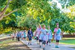 Costumed Women Walking In Color Frenzy Fun Run. MACKAY, QUEENSLAND, AUSTRALIA - JUNE 2019: Unidentified women wearing skirts and head pieces splattered with royalty free stock photo