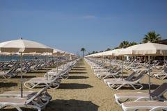 Mackenzie sandy beach at Larnaca, Cyprus. Sun loungers and umbrellas. Blue sky background, closeup view. Stock Photos