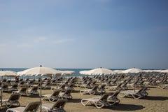Mackenzie sandy beach at Larnaca, Cyprus. Sun loungers and umbrellas. Blue sky background, close up view. Stock Photos