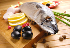 Mackerel. Fresh mackerel with olives, lemons and onions over wooden chopping board Royalty Free Stock Images