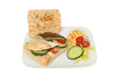 Mackerel fillets on ciabatta. Bread with salad on a plate isolated against white Royalty Free Stock Photo