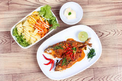 Mackerel fish fried topped spicy curry served with salad. Royalty Free Stock Photography