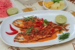 Mackerel fish fried topped spicy curry with side dish. Selective focus. Royalty Free Stock Image