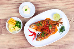 Mackerel fish fried topped spicy curry with side dish on wood. Stock Images