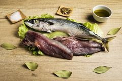 Mackerel fresh fish on lettuce leaves next to bay leaves, a few pieces of lemon, a bowl of oil and some spices on a wooden table. Prepared for cooking stock images
