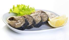 Mackerel. Pieces of mackerel and lemon on a white plate on a white background Royalty Free Stock Photos