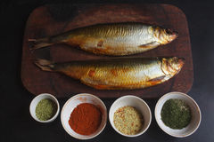 Mackerel smoked with spices. Mackerel smoked on a cutting board. And spices: fennel, paprika and herbs and assorted vegetables granulated Stock Photos
