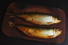 Mackerel smoked. Two mackerel smoked on a wooden cutting board Royalty Free Stock Images