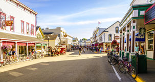 Mackinac Island. Michigan, August 8, 2016: Vacationers take on Market Street on  that is lined with shops and restaurants. No motorized vehicles are allowed on Royalty Free Stock Photography
