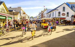 Mackinac Island. Michigan, August 8, 2016: Vacationers take on Market Street on  that is lined with shops and restaurants. No motorized vehicles are allowed on Stock Photography
