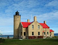 Mackinac Point Lighthouse. With the Machinac Island Bridge in the background.  Building has a vibrant red roof against a beautiful blue sky with clouds.  Green Stock Images