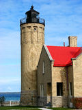 Mackinac Point Lighthouse. Old Mackinac Point Lighthouse with the Machinac Island in background.  Building has a vibrant red roof against a beautiful blue sky Royalty Free Stock Photography