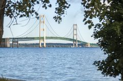 Mackinaw Bridge framed by trees. On a sunny day, historic landmark, engineering marvel, five mile suspension bridge, lake michigan, lake huron, great lakes Stock Photos