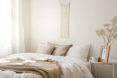 Macrame above comfortable king size bed. With white bedding, beige pillows and blanket, real photo stock photography