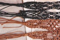 Macrame belts. Macrame skin belts on the woven background Stock Photo
