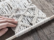 Macrame. Girl weaves macrame. White thread, female hand, wooden background, closeup.  royalty free stock images