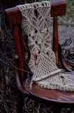 Macrame handmade on a wooden chair in the garden. The background of dry branches Stock Image