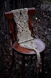 Macrame handmade on a wooden chair in the garden. The background of dry branches Royalty Free Stock Photos