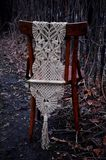 Macrame handmade on a wooden chair in the garden. The background of dry branches Royalty Free Stock Photography