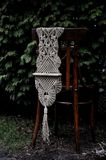 Macrame handmade on a wooden chair in the garden. Background of fir branches, thuja Stock Photos