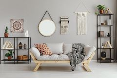 Macrame, mirror and ethno graphic on beige wall. In stylish living room interior with metal furniture and comfortable couch and patterned pillow and blanket royalty free stock photo