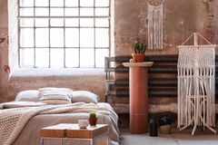 Macrame in a wabi sabi bedroom interior with a bed, table and stand with a plant. Real photo royalty free stock images