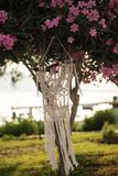 Macrame hanging from oleander tree. Macrame wall art hanging from the pink oleander tree Stock Image